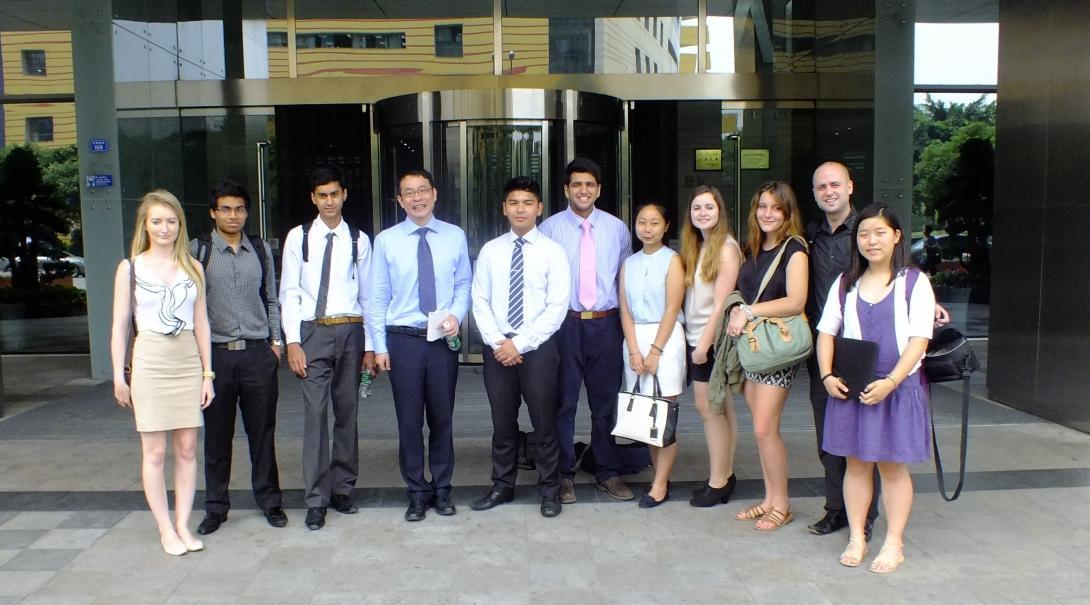 International business interns and local professionals pose outside a modern office block.